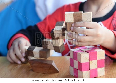 child's hands playing with colorful wooden bricks.5 year old boy playing wooden toy puzzle.Happy kid learning by play wooden toy