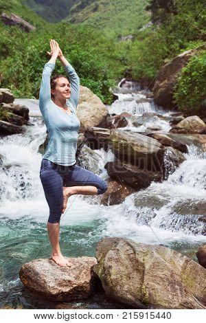 Woman in Hatha yoga balance yoga asana Vrikshasana tree pose at waterfall outdoors