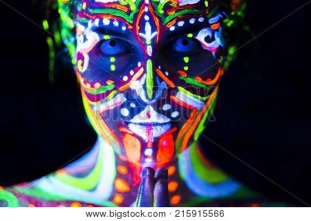 Close-up Portrait of an attractive young praying girl in bright blacklight bodyart poster