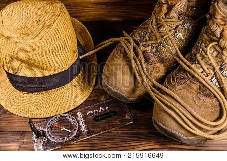 Touristic Magnetic Compass, Boots And Hat On Wooden Table. Top View