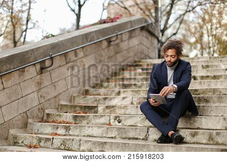 Mulatto boy using social networks on tablet and waiting girlfriend before date, sitting on steps. Young boy looking handsome in dark classic suit. Concept of romantic youth and Internet virtual communication.