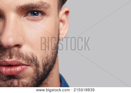 Thoughtful look. Close up of serious young man half face looking at camera while standing against grey background