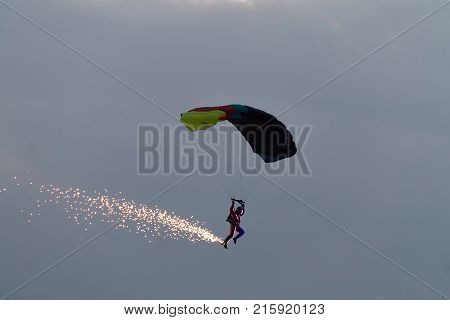 Parachutist at an air show with fireworks and lights