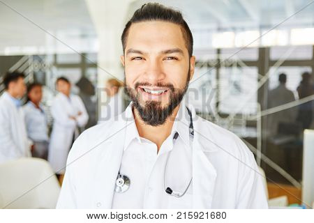 Smiling chief physician with team in hospital as competent doctor
