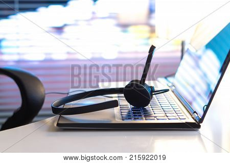 Help desk 24/7 customer service support hotline or call center concept. Headset on laptop keyboard late at night in office. Video call conference or telemarketing.