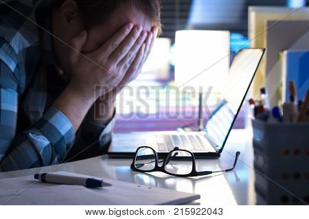 Problems at work. Sad unhappy and tired man covering face with hands in office or home at night. Burnout stress workplace bullying or depression concept. Glasses on table.