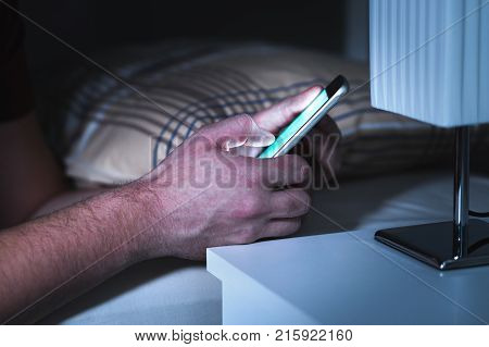 Man using smartphone in bed late in the middle of the night. Mobile phone in bedroom. Texting or using social media. Cellphone addiction.