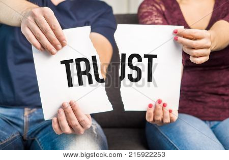 No trust. Cheating infidelity marital problems having an affair and another partner betrayal mistrust or being unfaithful concept. Couple man and woman ripping same paper.