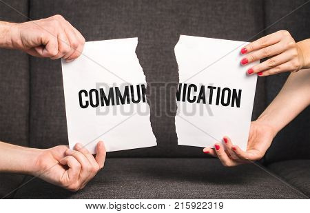 Communication problem in relationship. Marital difficulties. Couple fighting. Man and woman holding ripped paper.