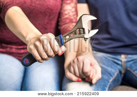 Fixing relationship problems concept. Couple holding hands in therapy and counselling session. Woman or wife showing a tool and wrench.