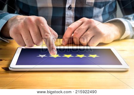 Good review. Satisfied and happy customer giving great rating with tablet on an imaginary criticism site application or website. Four out of five stars. Man using mobile device home.