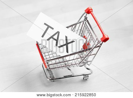 Tax taxation and VAT concept. Shopping cart with a card or paper sign.