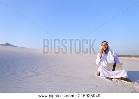 Modern male Arab and builder dials on cellular customer to clarify stages of construction and sits with computer on white clean sand outdoors on hot summer day. Smiling Muslim with short dark hair dressed in kandura, long spacious dress of white unpainted