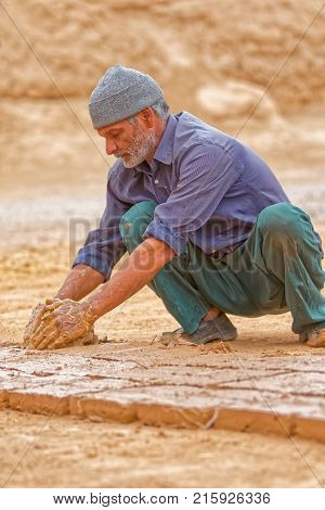 MEYBOD, IRAN - MAY 6, 2015: Brickman making the clay bricks in traditional way in Iran.