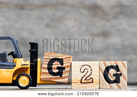 Yellow plastic forklift hold letter G to complete word G2G (Government to government) on wood background