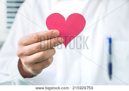 Doctor holding red heart. High blood pressure heart attack or disease concept.