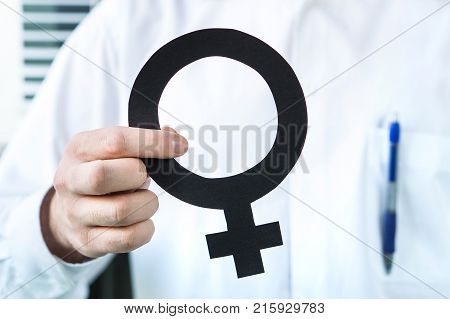 Female health concept. Doctor holding woman symbol. Specialist gynecologist or obstetrician.