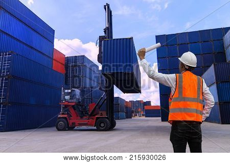 Forklift truck lifting cargo container in shipping yard for transportation import export business.