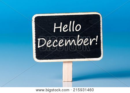 Hello december on sign at blue background. December 1st, the beginning of the Christmas and New Year holidays and sales.