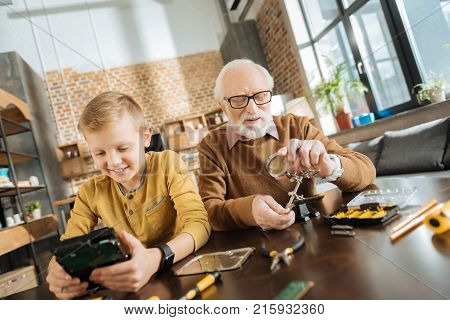 Common interests. Positive cheerful nice grandfather and grandson sitting together and enjoying their time while being interested in fixing objects