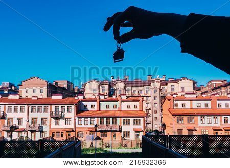 Male hand holding house keys on house shaped keychain. Human hand silhouette holding keychain in form of house with key on the background a new buildings.