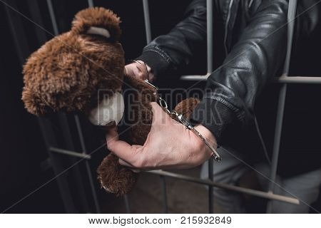A man in handcuffs is behind bars in a police station. He was jailed. In his hands he keeps a toy bear. He is very angry that was caught by the police.