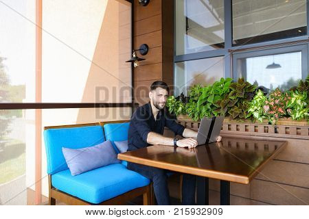 Prosperous businessman looking at camera and talking. Handsome male person dressed in black shirt sitting near indoor plants. Concept of achieving success and using modern technologies for biz and employment.
