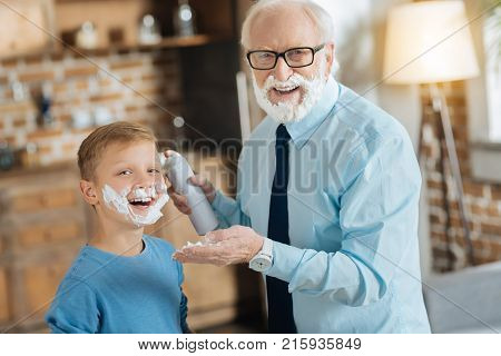 Time for shaving. Happy nice elderly man holding shaving foam and smiling to you while standing together with his grandson