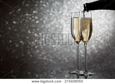 Picture of bottle with flowing champagne in wine glasses on gray background