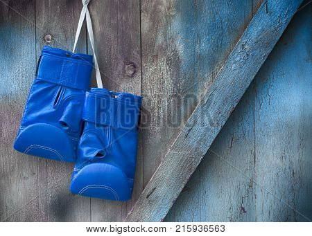 Blue boxing gloves hang on a nail on a wooden shabby wall empty space on the right