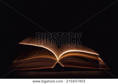 Closeup view on old open book in the dark.
