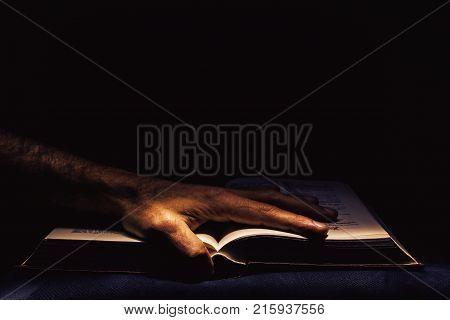 Man's hand on open book, studio shot in the dark.