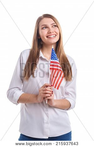 A beautiful, young girl in a white shirt and jeans with a smile holding an American flag on a stick against a white isolated background