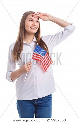 A young, happy girl with a cute smile in a white shirt salutes with an American flag on a stick on a white isolated background
