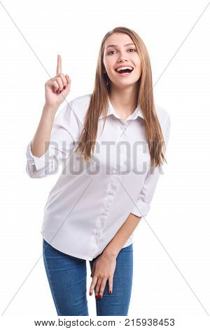 Beautiful girl with a cute smile in a white shirt keeps her index finger up on a white isolated background