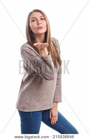 Beautiful young girl wearing a sweater sends an air kiss on a white isolated background