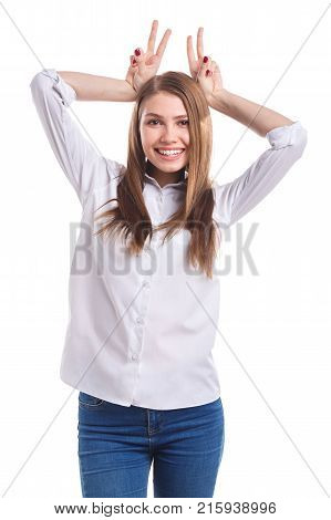 A young, happy girl with a sweet smile in a white shirt has made herself a bunny ears with her hands on a white isolated background