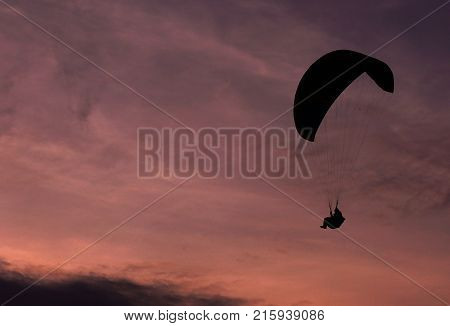 The silhouette of the parachutist on the background of the crimson sunset.