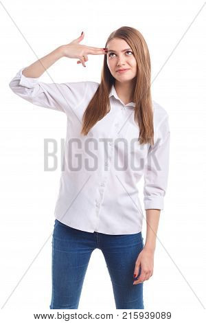 A young, beautiful girl in a white shirt has put her hand to the head like a gun and is looking up on a white isolated background