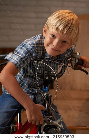 Smiling boy tightening the screw of his bicycle