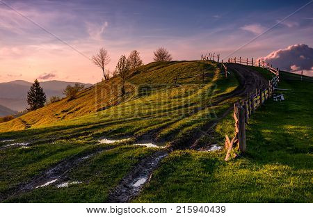 wooden fence along the country dirt road uphill the grassy knoll in springtime at dusk. Spectacular nature scenery in mountainous rural area with gorgeous pink sky with some clouds