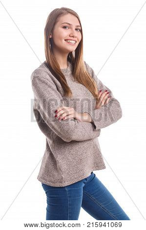 A young, beautiful girl in a gray sweater with a smile folded her hands standing half-turned on a white isolated background