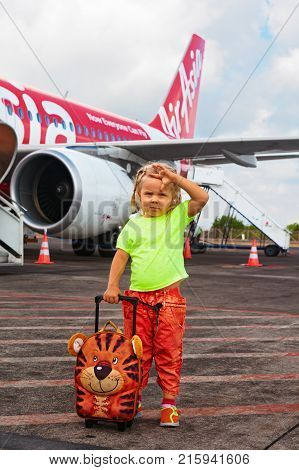 DENPASAR BALI ISLAND INDONESIA - August 27 2015: Cute child wait for boarding to plane in International Bali airport I Gusti Ngurah Rai. Little passenger carrying luggage to airplane.