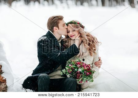 Groom is kissing his bride on the temple on the white snow background. Winter wedding. Artwork. Selective focus on the bouquet. Copy space