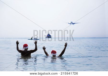Two Men In Santa Claus Red Hat Sit On The Beach In Morning Hangover Christmas Holiday Party Dreams