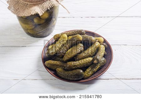 Pickles . Marinated cucumber in plate on stone background .