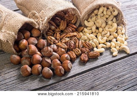 Mix of nuts . Hazelnut pecan and cashew in burlap bag on wooden background . Healthy food