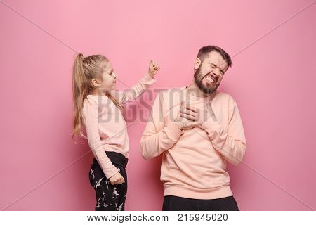 Young father with his baby daughter. The kid in preschool age pointing with finger and scolding father