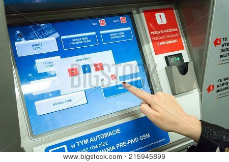 WARSAW POLAND - MAY 22 2017: Close up of woman buying public transportation tickets from machine in Warsaw. Public transportation in Warsaw consists of tram train bus and subway.