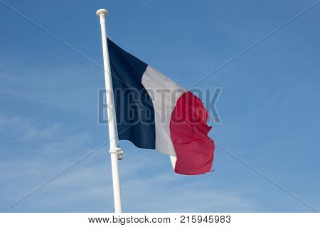 red white blue french flag flutters in the sky hanging on a mast